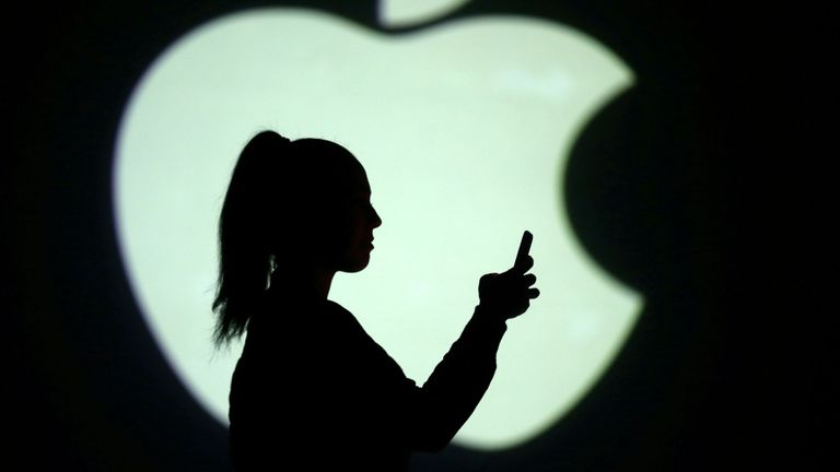 Silhouette of mobile user is seen next to a screen projection of Apple logo in this picture illustration taken March 28, 2018.