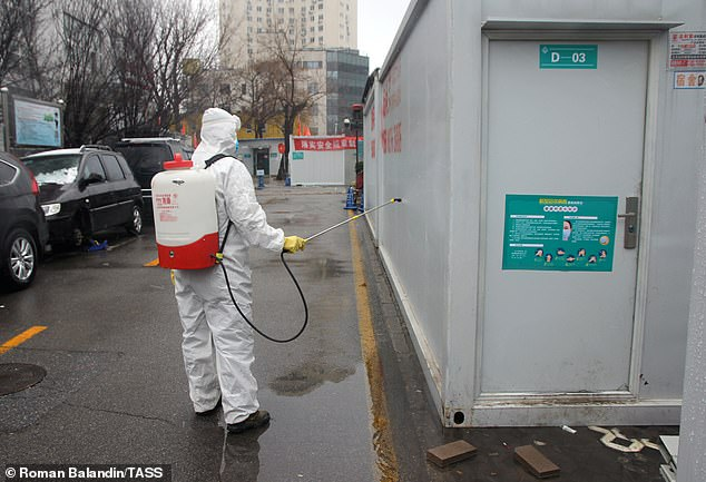 A person is pictured spraying disinfectant on a building at theChaoyang An'yuan Hospital in Beijing