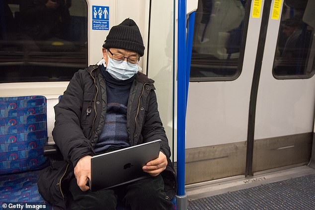 A passenger wears a face mask while riding the London Underground yesterday as infections rapidly approached triple digits in the UK