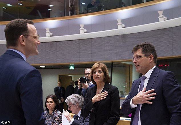 European Commissioner for Health Stella Kyriakides, center, and European Commissioner for Crisis Management Janez Lenarcic, right, put their hands over their hearts in a gesture of hello to German Health Minister Jens Spahn during an extraordinary meeting of EU health ministers