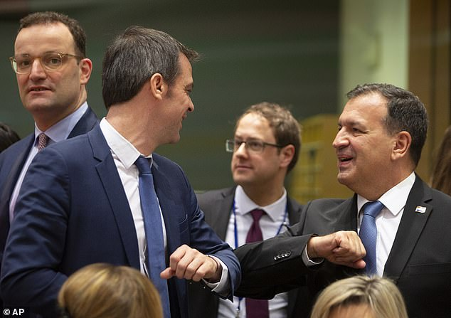 European health chiefs greeted each other with elbow bumps at an emergency meeting being held in Brussels today. Pictured,Croatian Health Minister Vili Beros, right, bumps elbows to say hello to French Health Minister Olivier Veran