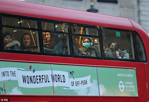 One in ten Britons could end up in hospital with coronavirus according to NHS officials who are drawing up a 'battle plan' to tackle the deadly outbreak. Pictured: A woman wearing a face mask on a London bus